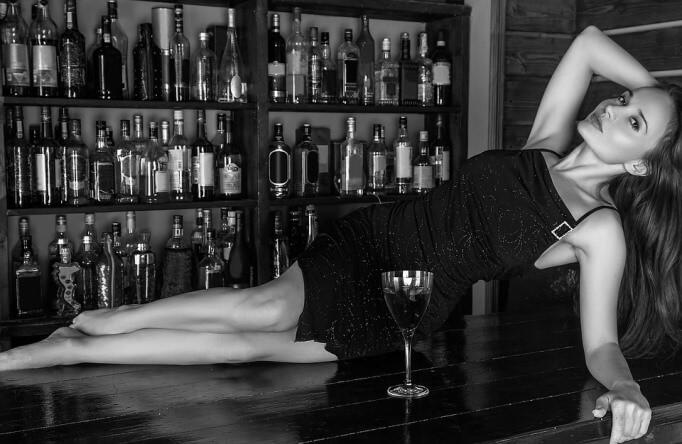 Женщина на столе с бокалом вина