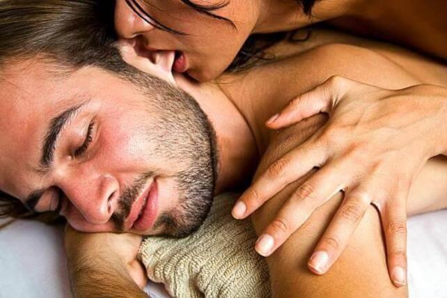 Женщина целует ухо мужчине
